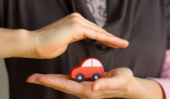one hand holding a small, red toy car, one hand above it