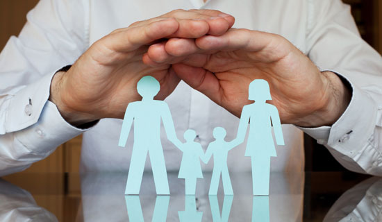 two hands held above paper cutout figures of a family