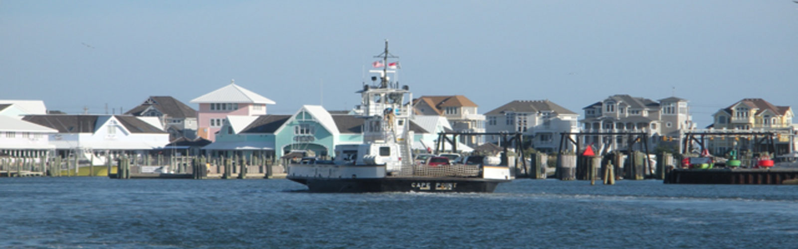 a boat on the water in the foreground, shore homes in the background