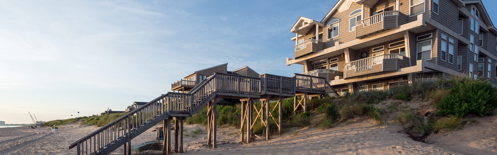 a large beach house with a wooden boardwalk/stairs