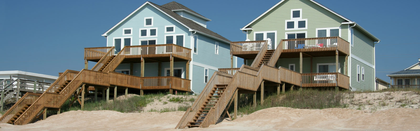 two large beach houses with wooden decks/stairs